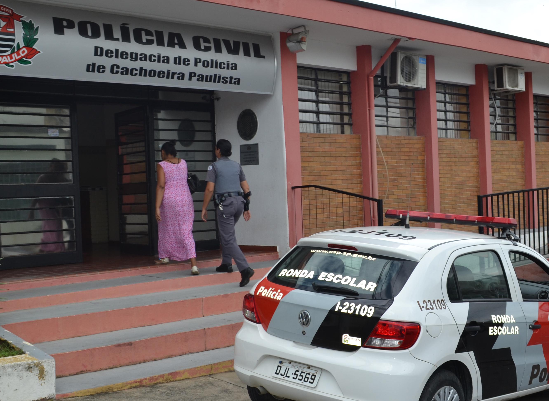Mãe adotiva da vítima entra na delegacia acompanhada de policial (Francisco Assis)