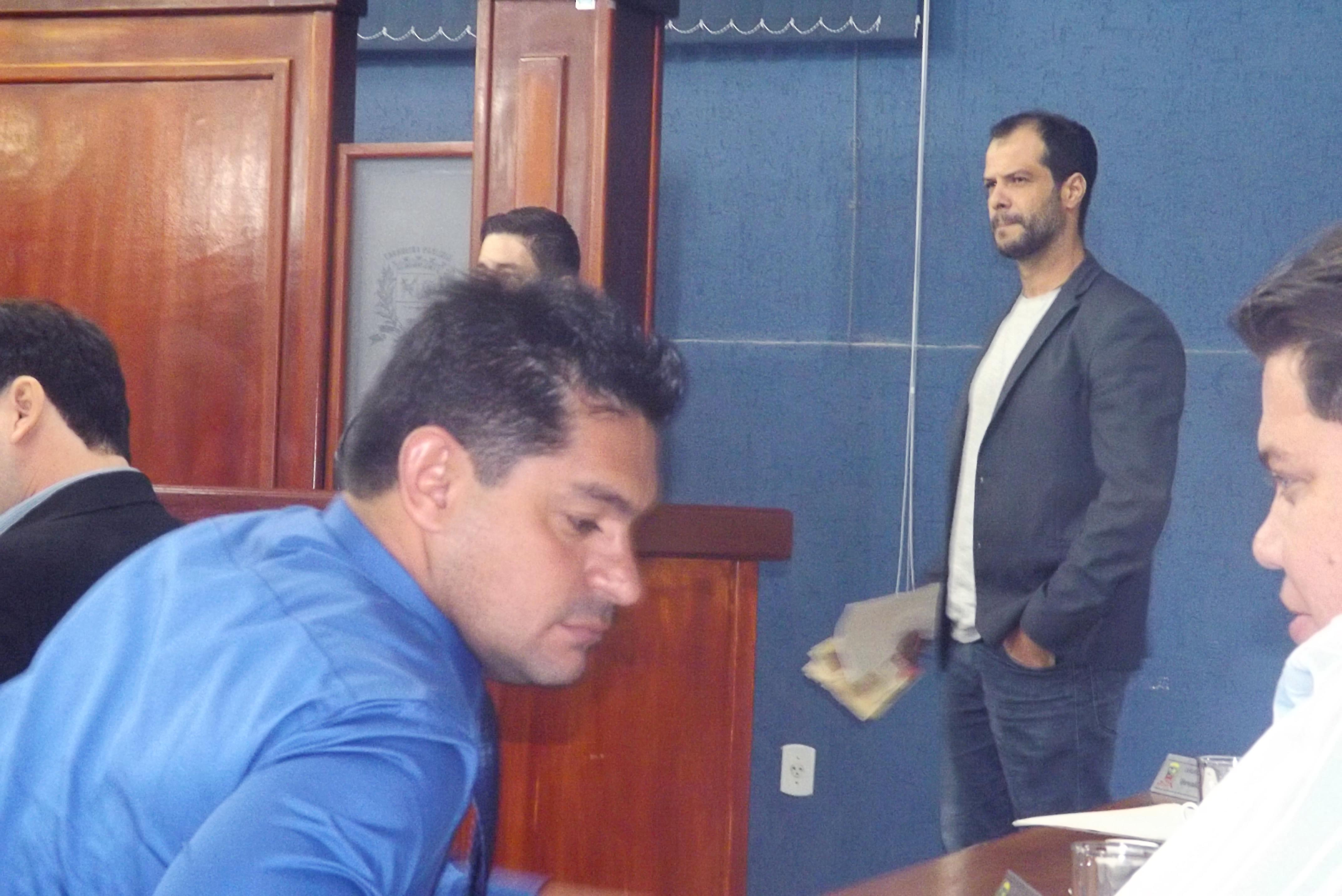 Max Miranda tenta se acomodar na cadeira durante sessão, com Claudio Gaspar, em pé, próximo à tribuna; clima ficou tenso na terça-feira (Arquivo Atos)