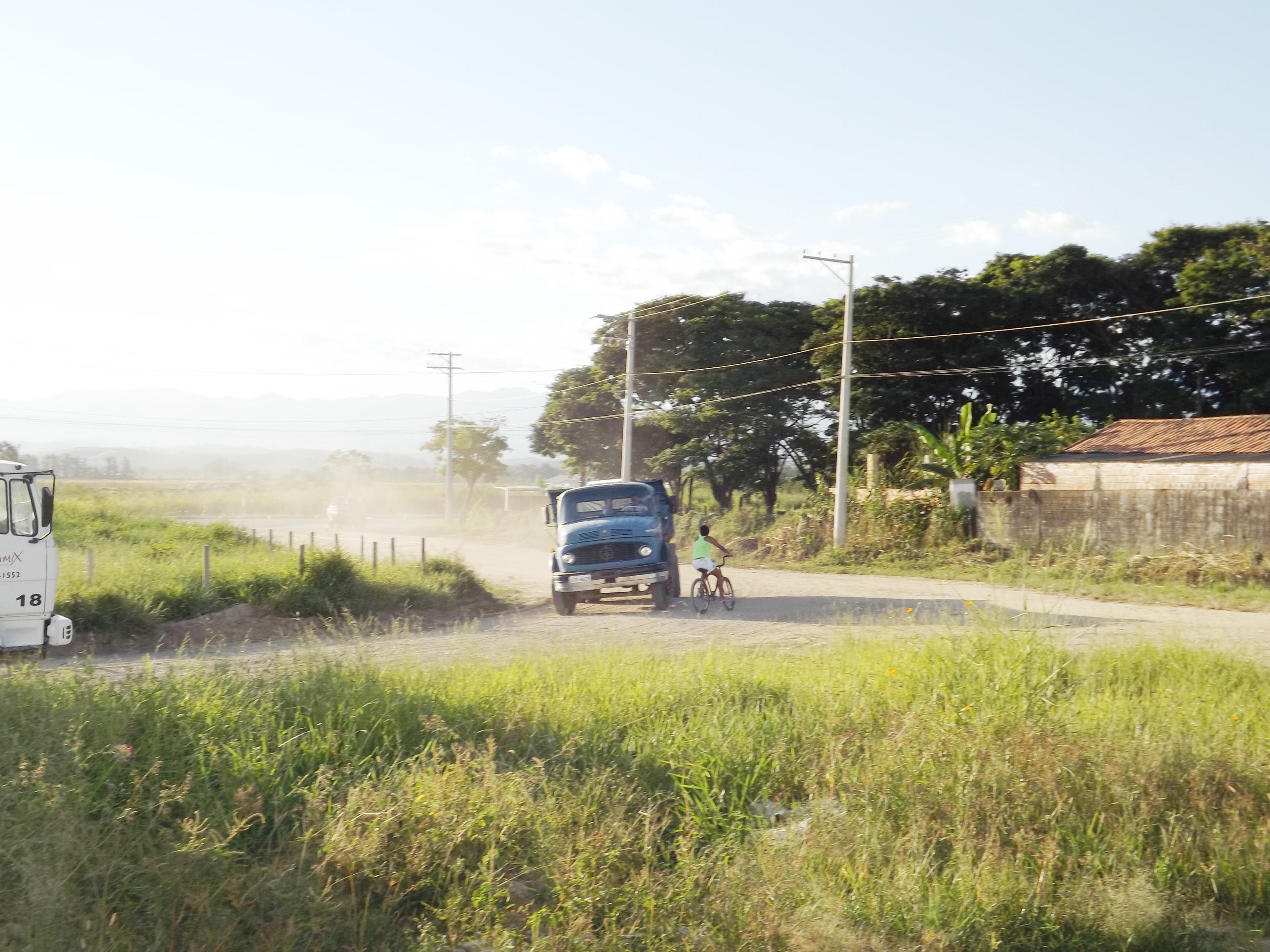 Estrada de terra e mato alto dão mostras dos problemas no bairro, próximo ao polo industrial em Canas (Lucas Barbosa)