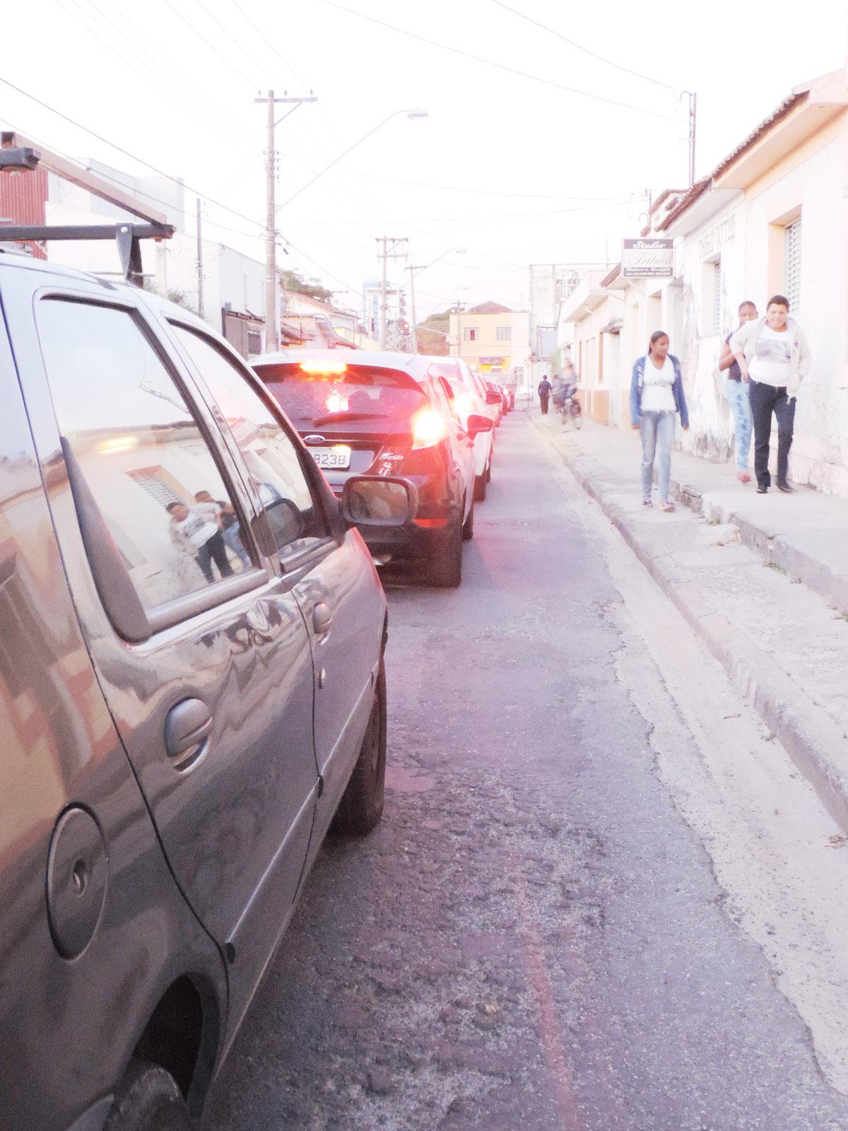 Carros enfileirados na rua Padre João Renaudin, principal acesso à rodoviária; cidade tenta se organizar (Foto: Rafaela Lourenço)