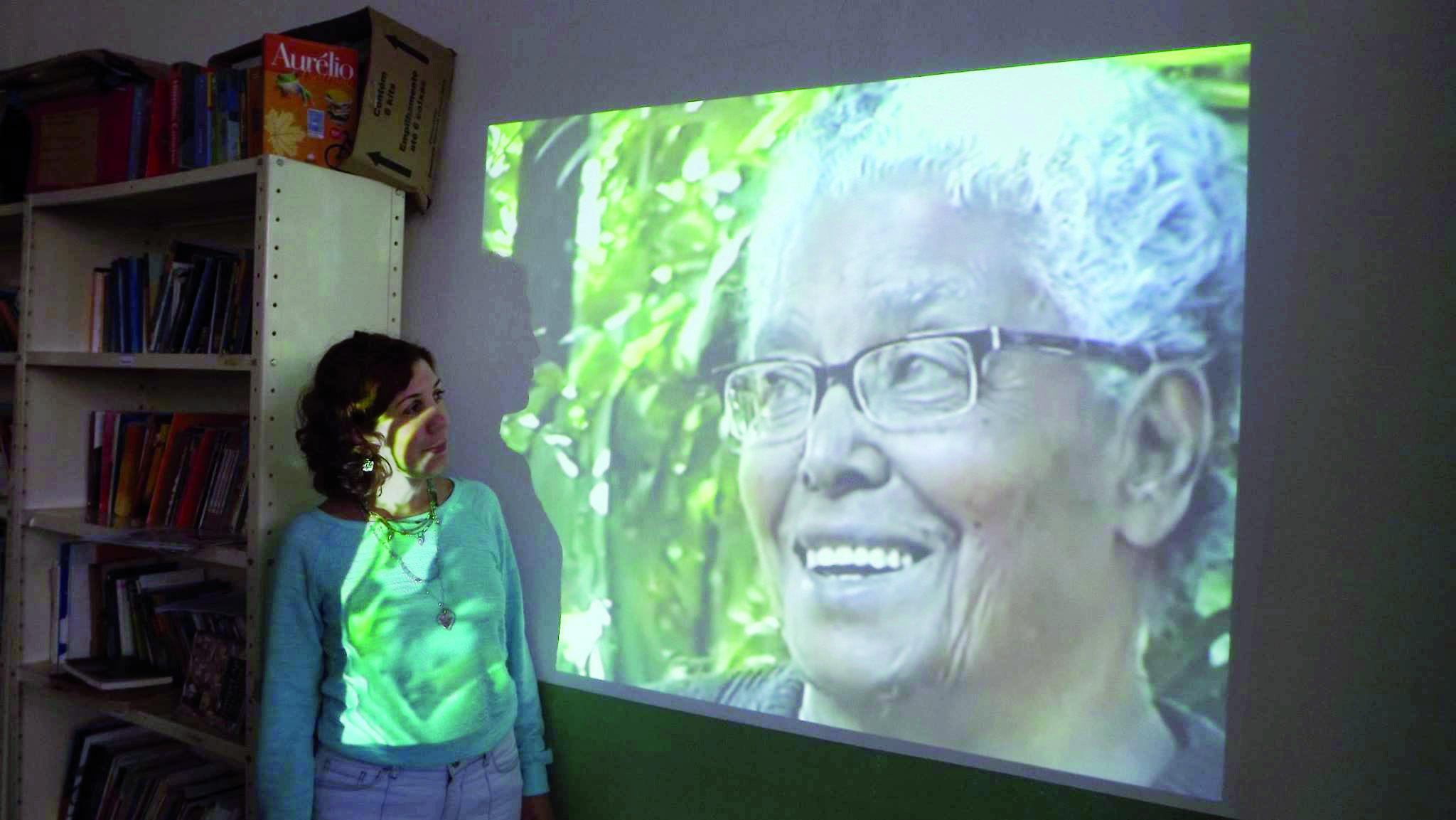 Junia Botelho, filha de Ruth, em frente à imagem da mãe, durante evento que homenageia a escritora (Foto: Reprodução)