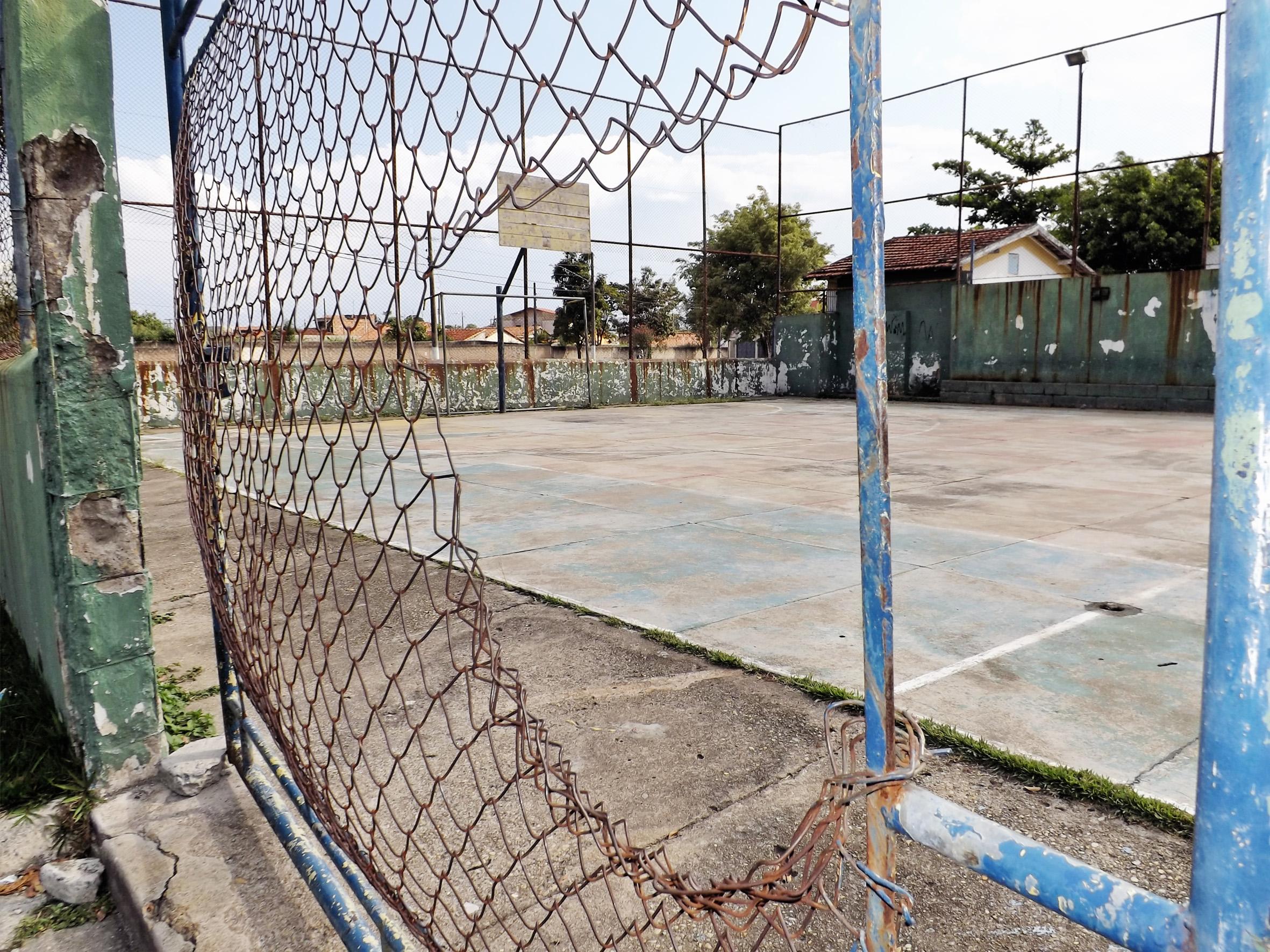 Alambrado destruído, tabelas de basquete sem aro, piso com irregularidades; cenário mostra abandono de quadra esportiva em Cachoeira (Foto: Lucas Barbosa)