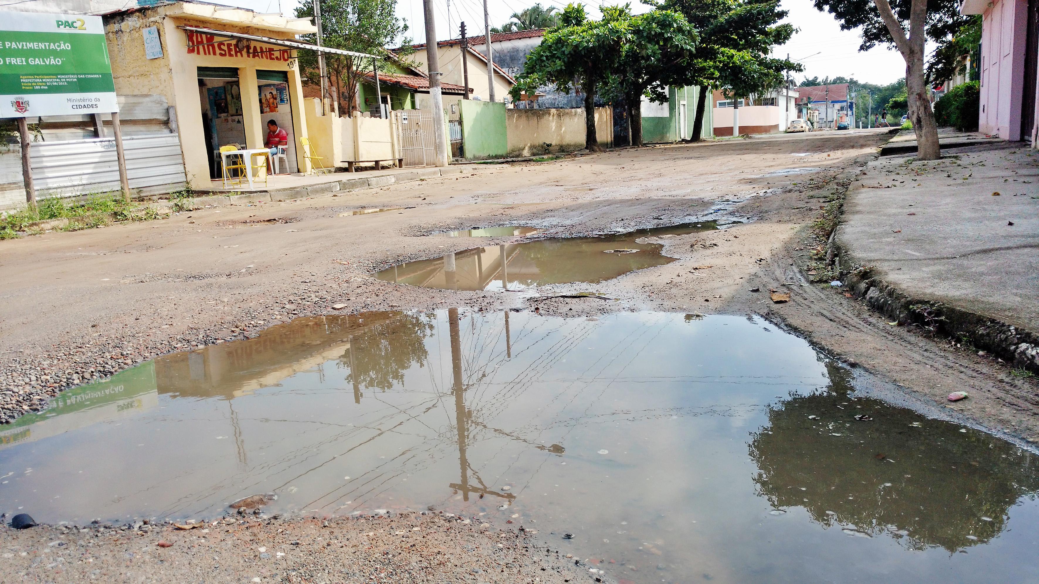 Placa (no alto, à esquerda) informa obra de pavimentação que nem mesmo foi iniciada em Potim; moradores cobram trabalhos da Prefeitura (Foto: Rafael Rodrigues)