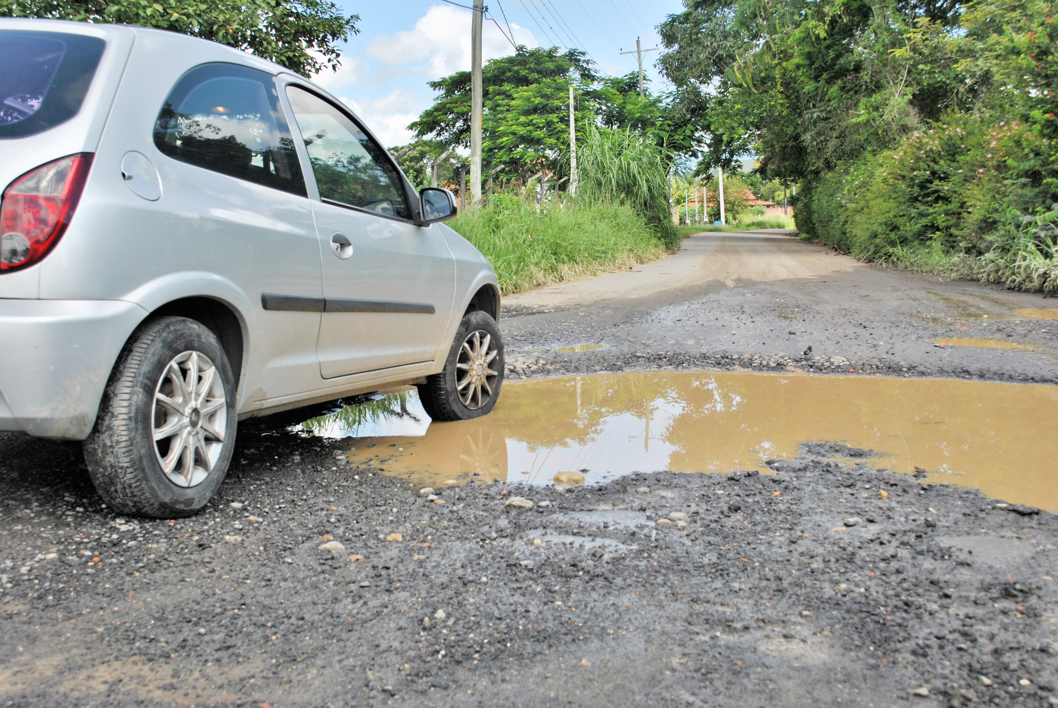 Motorista enfrenta obstáculo causado por descaso com asfaltamento em rua do Washington Beleza (Foto: Andreah Martins)