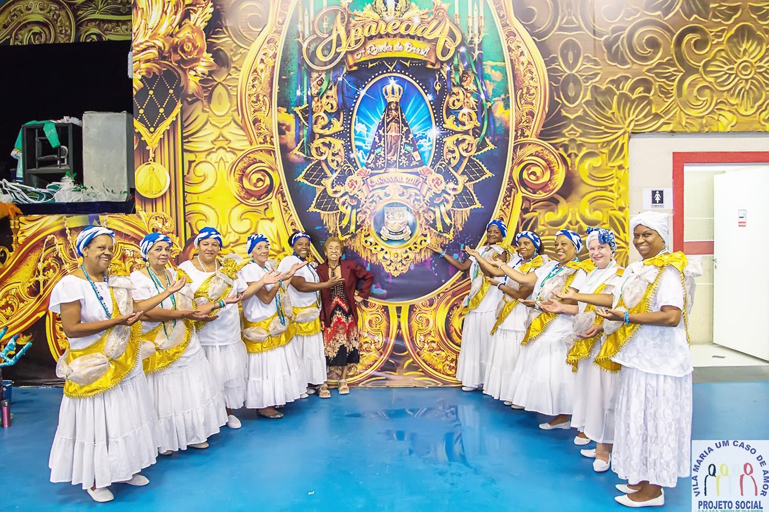 Baianas da Vila Maria posam ao lado da bandeira de Nossa Senhora Aparecida; homenagem à santa (Foto: Reprodução)