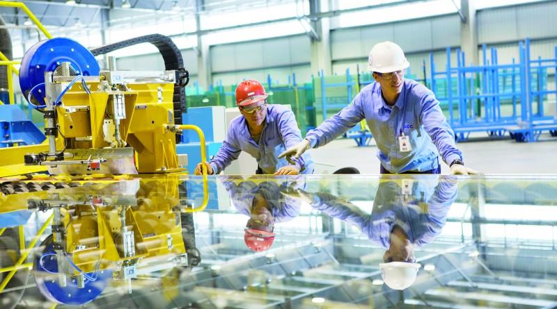 Funcionários da AGC na linha de produção da multinacional em Guará (Foto: Reprodução)