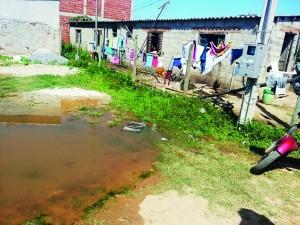Moradores de casas no Santa Edwiges, em Aparecida, um dos exemplos de falhas de saneamento no Vale (Foto: Arquivo Atos)