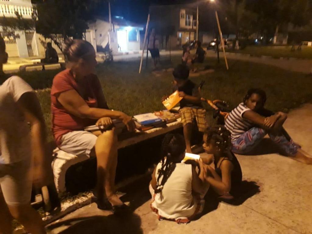 Voluntária lê ao lado de crianças atendidas pelo projeto em Potim; ação abre espaço também para adultos (Foto: Reprodução)
