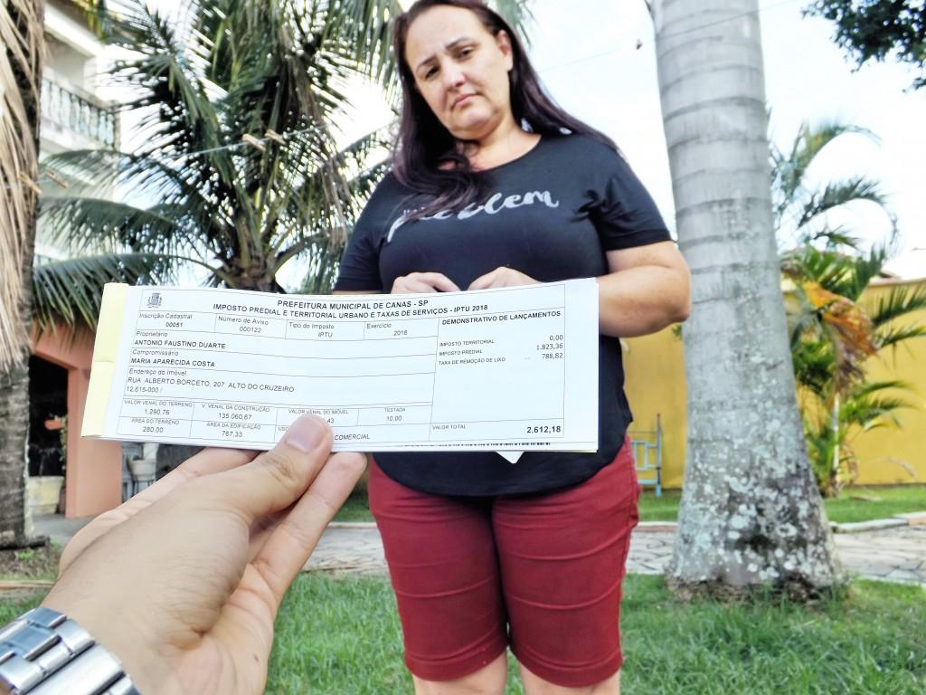 Moradores mostram carnê com valores elevados após reajuste do IPTU em Canas; cidade registra casos de até 900% de aumento no imposto (Foto: Lucas Barbosa)