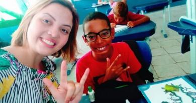 A professora Rayane Batista posa ao lado do pequeno Wellington de Souza, assistido por programa (Foto: Reprodução)